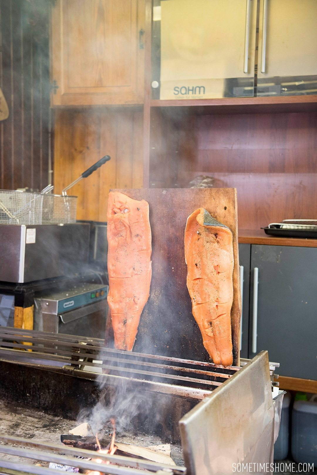 Travel tips with local cuisine - smoked salmon in a Christmas Market in Budapest. Image by Mikkel Paige, for travel blog Sometimes Home.
