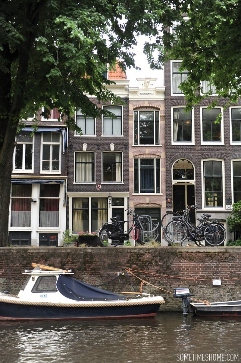 Things to do in Amsterdam besides smoking pot by travel blog Sometimes Home. View of the canals and row houses from the street.