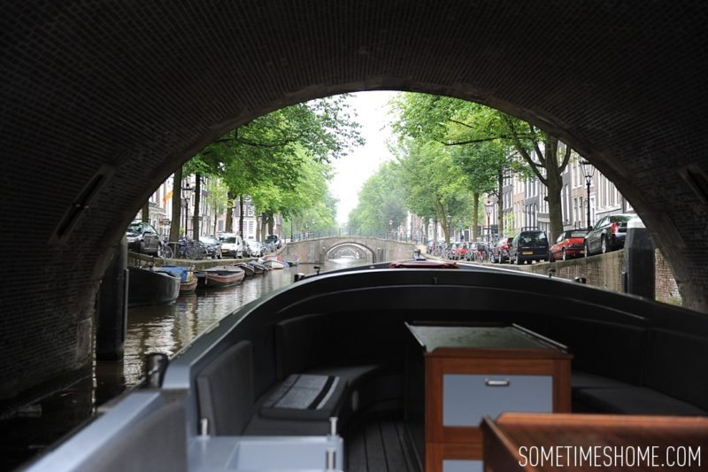 Things to do in Amsterdam besides smoking pot by travel blog Sometimes Home. View of the canals from under a brick bridge.
