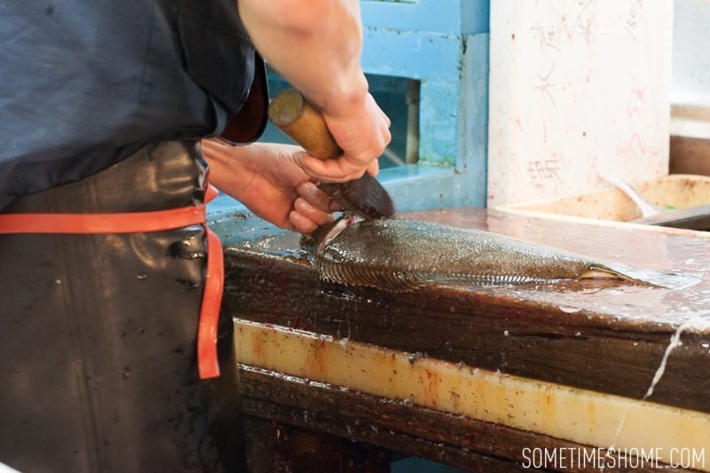 Experience and photos at Tsukiji Fish Market in Tokyo, Japan by Sometimes Home Travel Blog. Picture of a vendor cutting a fish.