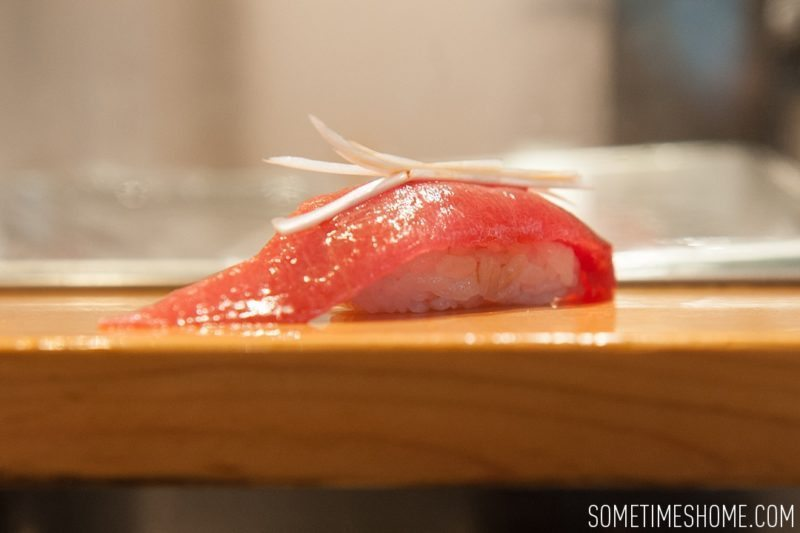 Sushi Dai Restaurant at Tsukiji Fish Market in Tokyo Japan. Photos on Sometimes Home travel blog with a picture of a tuna sushi piece.