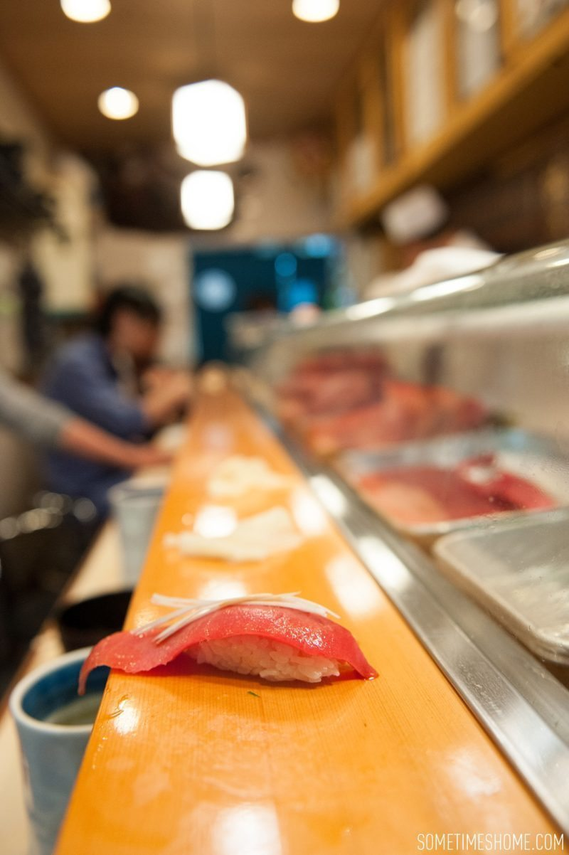 Sushi Dai Restaurant at Tsukiji Fish Market in Tokyo Japan. Photos on Sometimes Home travel blog with a picture of tuna at the bar.
