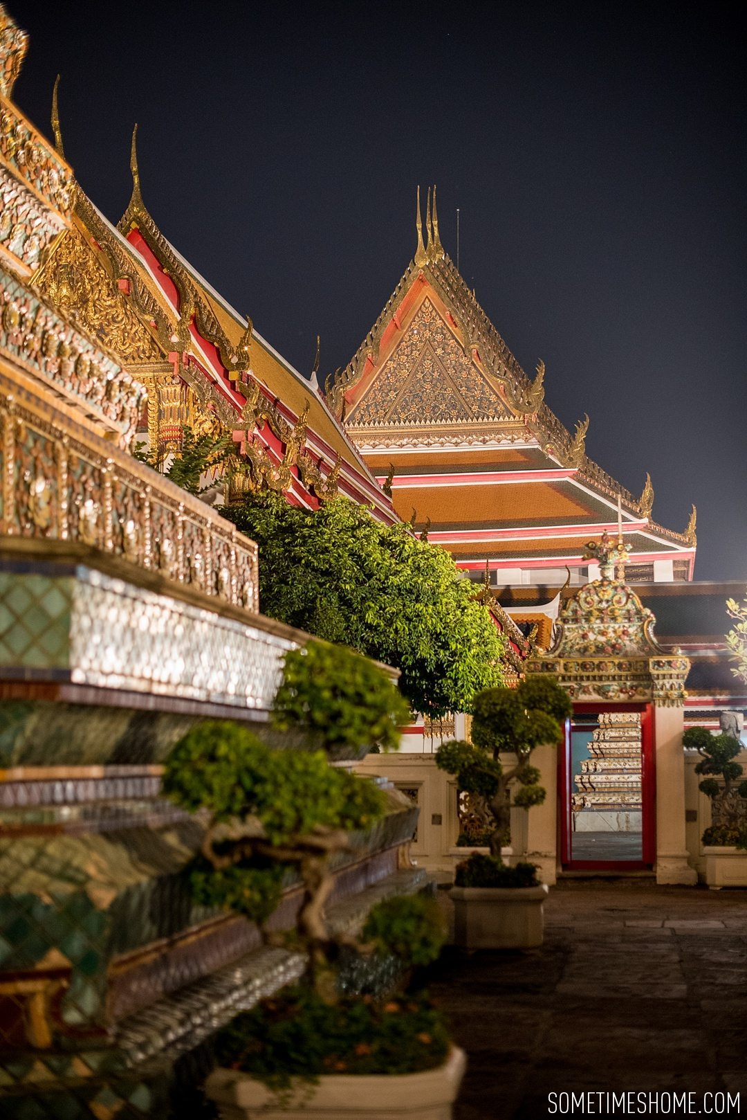Photos of a Bangkok Night Tuk Tuk Tour You Have To Take in Thailand by Sometimes Home travel blog. Expique tour with pictures of the famous Wat Pho in the evening with bonsai trees.