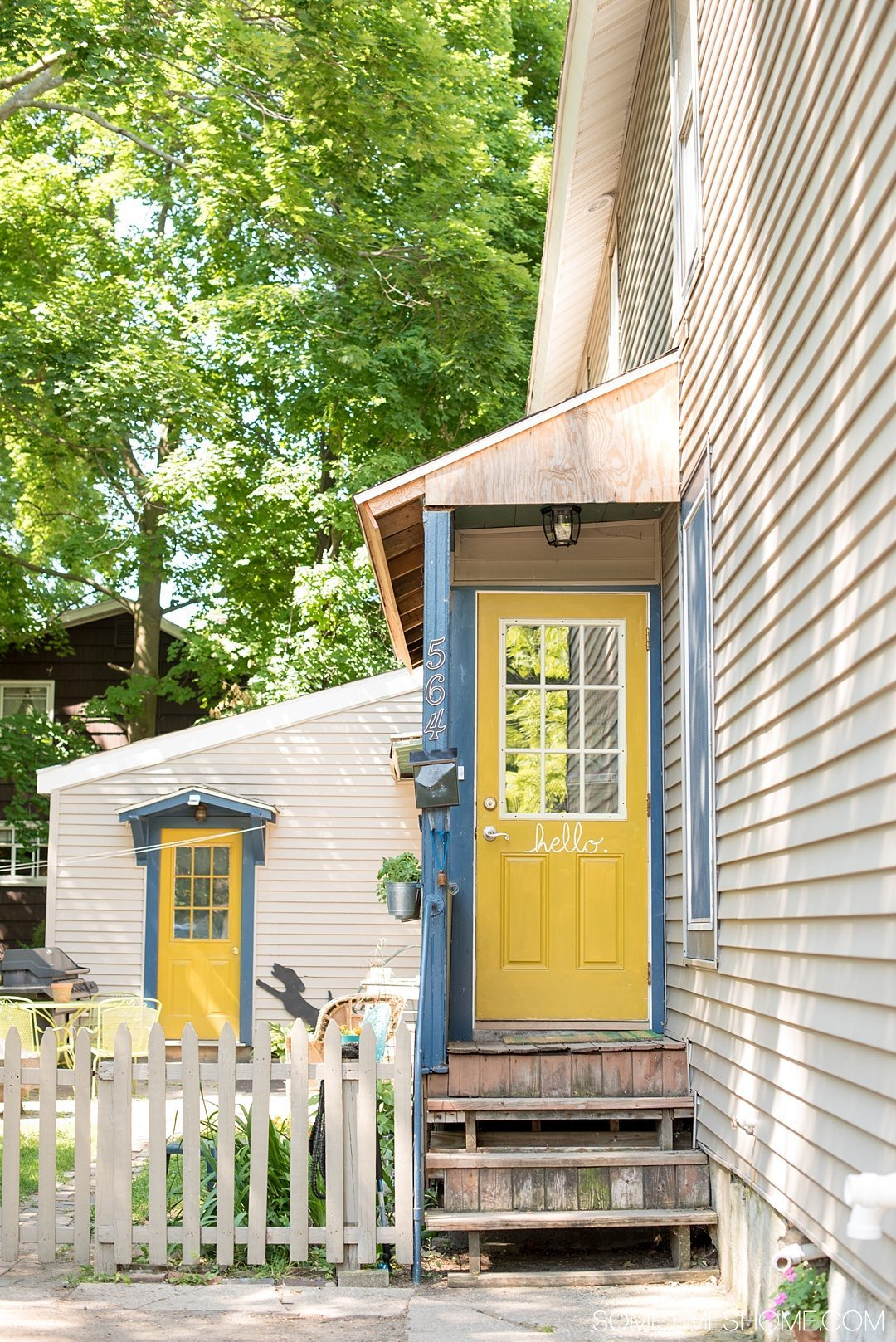 "Why a Trip to Buffalo Had Me in Disbelief on Sometimes Home travel blog. Photo of a ""hello"" house in yellow and blue in East Aurora, New York."