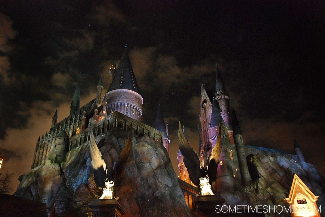 5 Mistakes to Avoid at the Wizarding World of Harry Potter in Orlando, Florida by Sometimes Home travel blog. Photo of Hogwarts Castle at night.