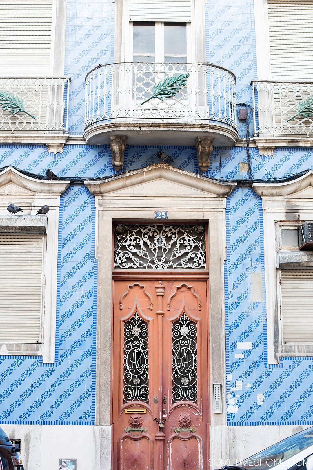 Why Lisbon is the Best City in Europe on Sometimes Home travel blog. Photo of blue hand painted tiles on the facade of a building.