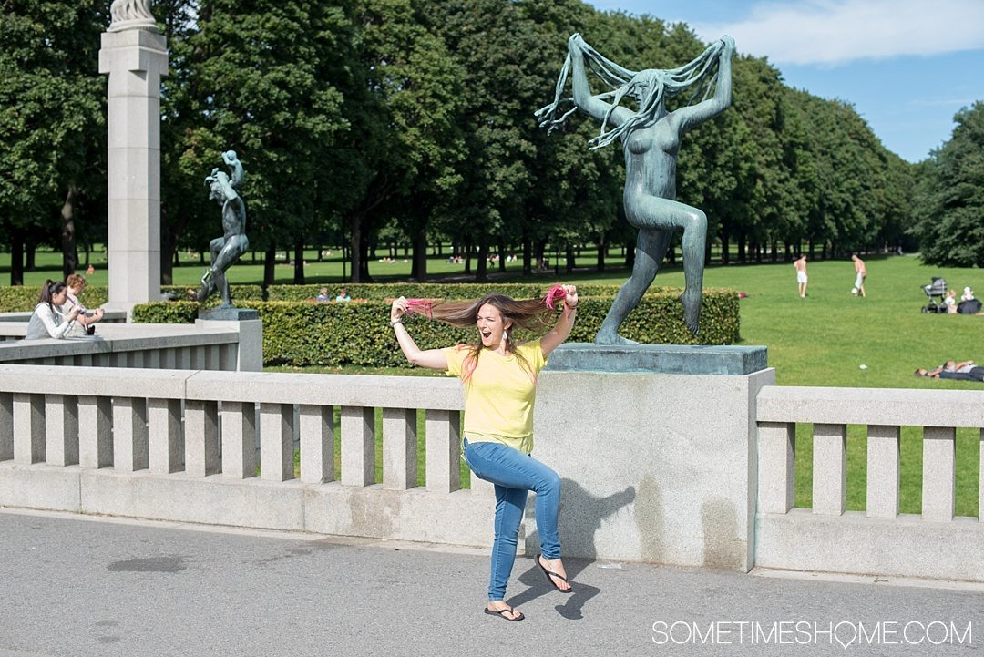 10 Not-to-Miss Sites in Oslo Norway by Sometimes Home travel blog. Photo of a female figure pulling her hair created in bronze, one of 200 statues in Vigeland Park.