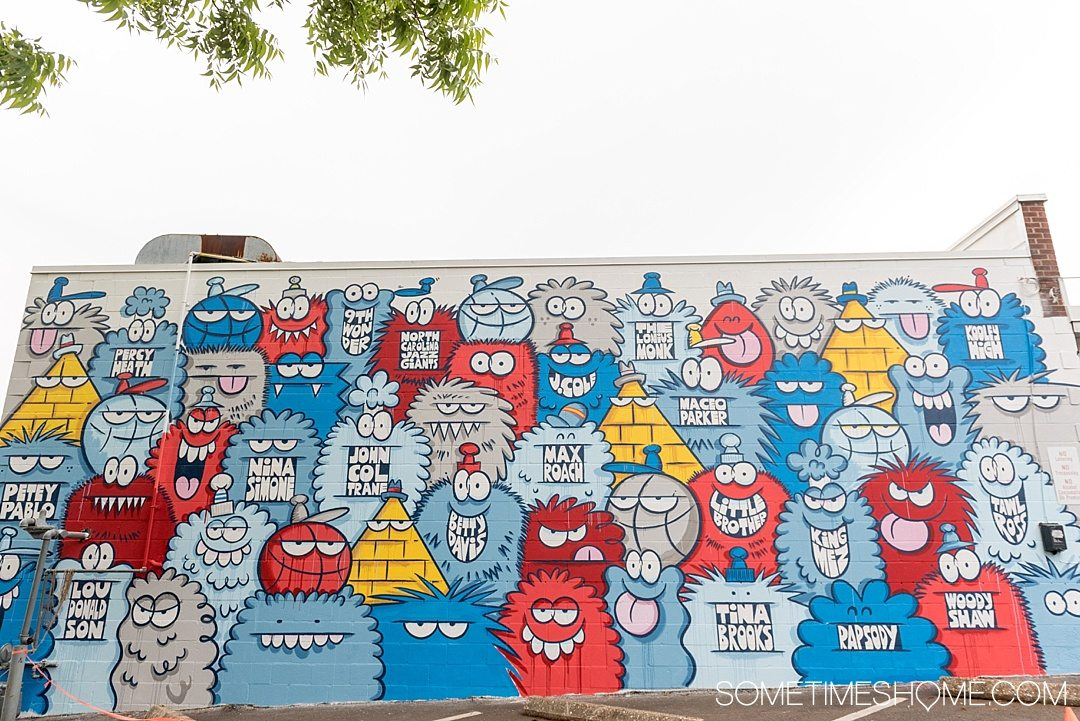 10 Best Downtown Raleigh Photography Spots on Sometimes Home travel blog. Photo of a mural wall by Kevin Lyon of colorful monsters in red, blue, grey and white near Trophy Brewing.