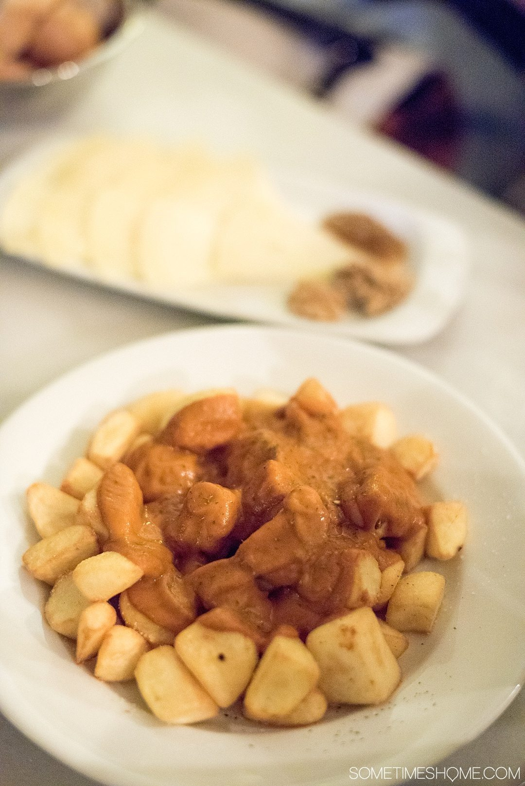 Eat Your Way Through Seville on Sometimes Home travel blog. Photo of patatas bravas, fried potatoes and gravy.