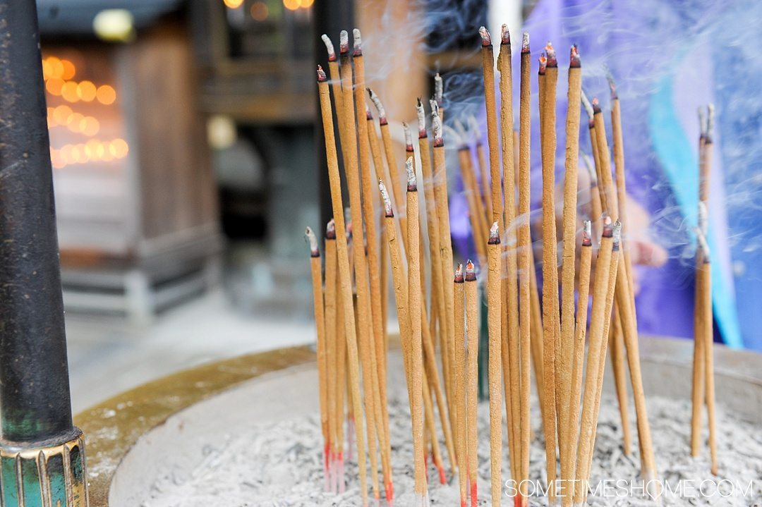 12 Inspiring Photos of Kyoto Japan on Sometimes Home travel blog. Picture of burning incense at the Golden Temple, Kinkaku-ji.