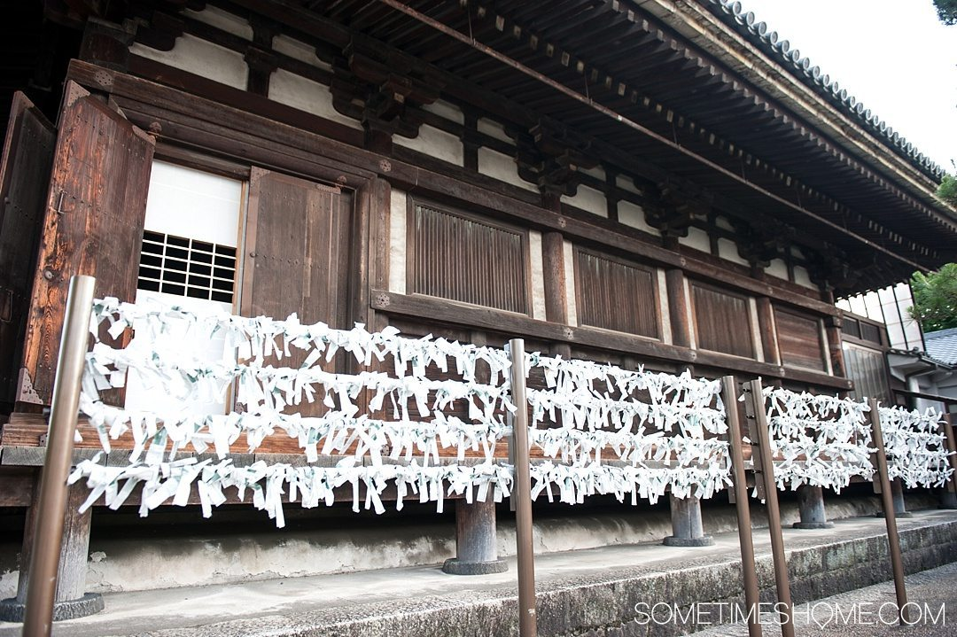 12 Inspiring Photos of Kyoto Japan on Sometimes Home travel blog. Picture of prayer paper at a temple at the Imperial Palace.