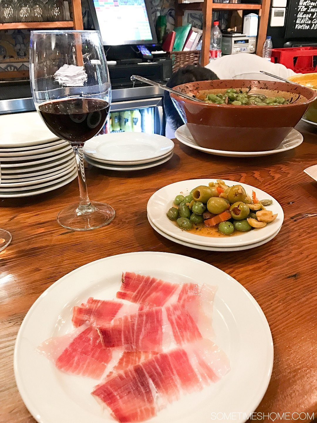 Eat Your Way Through Seville on Sometimes Home travel blog. Photo of olives and jamon iberica.