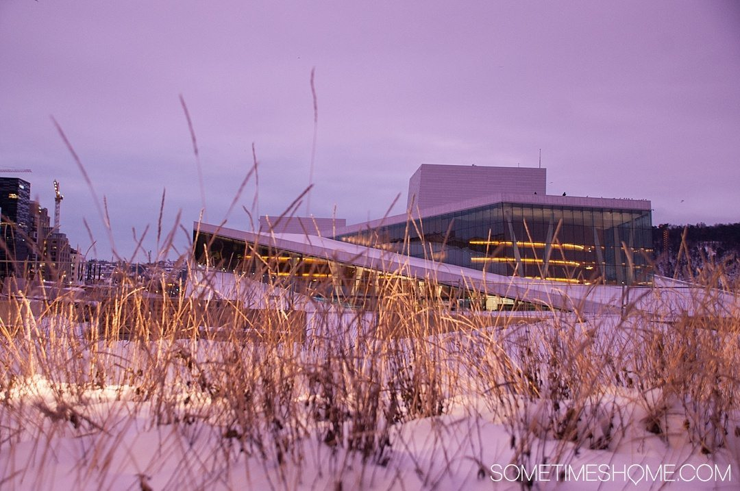 Reasons Why January is the Best Time to Visit Norway with a photo of the Opera House in Oslo during a pink sunrise, covered with snow.