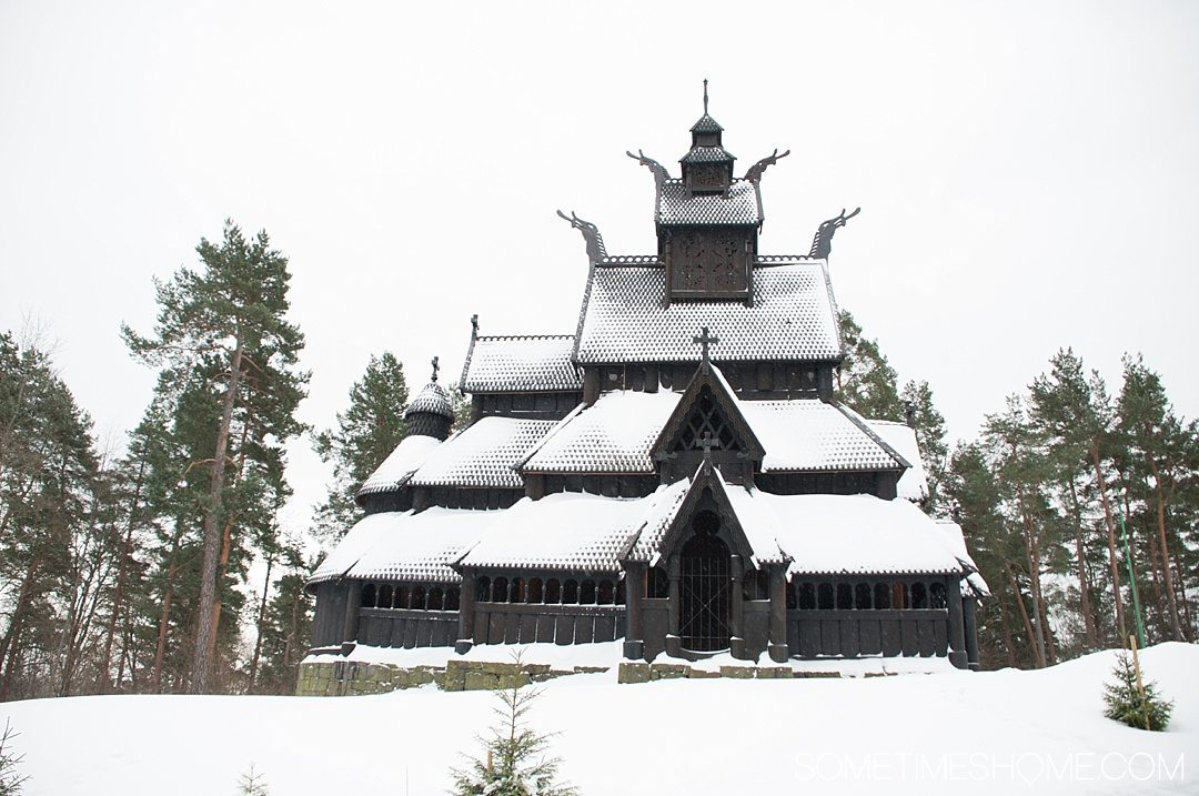 Reasons Why January is the Best Time to Visit Norway with a photo of a traditional wooden Stave Church covered in snow in Oslo's Norsk Folkemuseum.