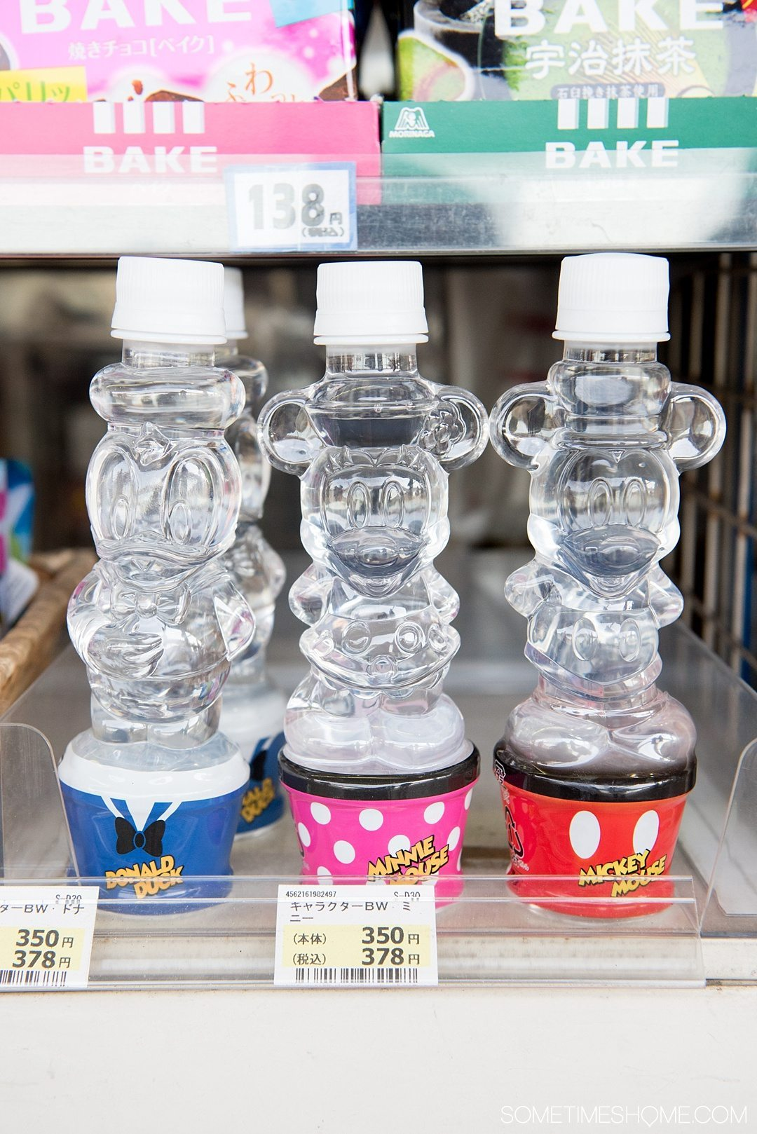 The Ultimate First-Timer's Guide to Tokyo DisneySea on Sometimes Home travel blog. Photo of Disney character shaped water bottles at a concession stand on the JR Maihama line station platform.