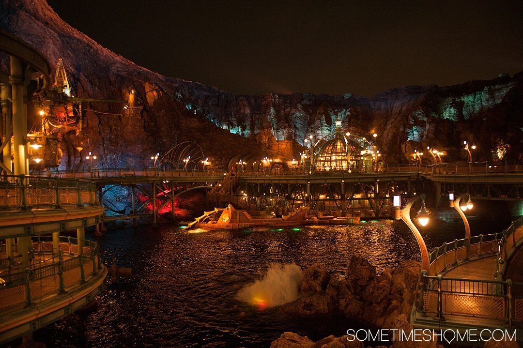 The Ultimate First-Timer's Guide to Tokyo DisneySea on Sometimes Home travel blog. Photo of the nautilus ship at 20,000 Leagues Under the Sea in Mysterious Island illuminated at night.