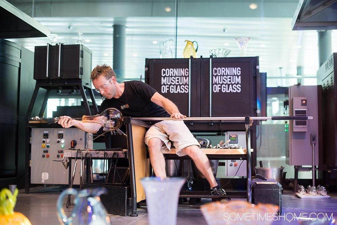 Corning Museum of Glass gift shop, hours, exhibits, photos and more on Sometimes Home travel blog. Also links to an article of what to do in Corning, New York in the Finger Lakes region. Picture of a demonstration of glass blowing.