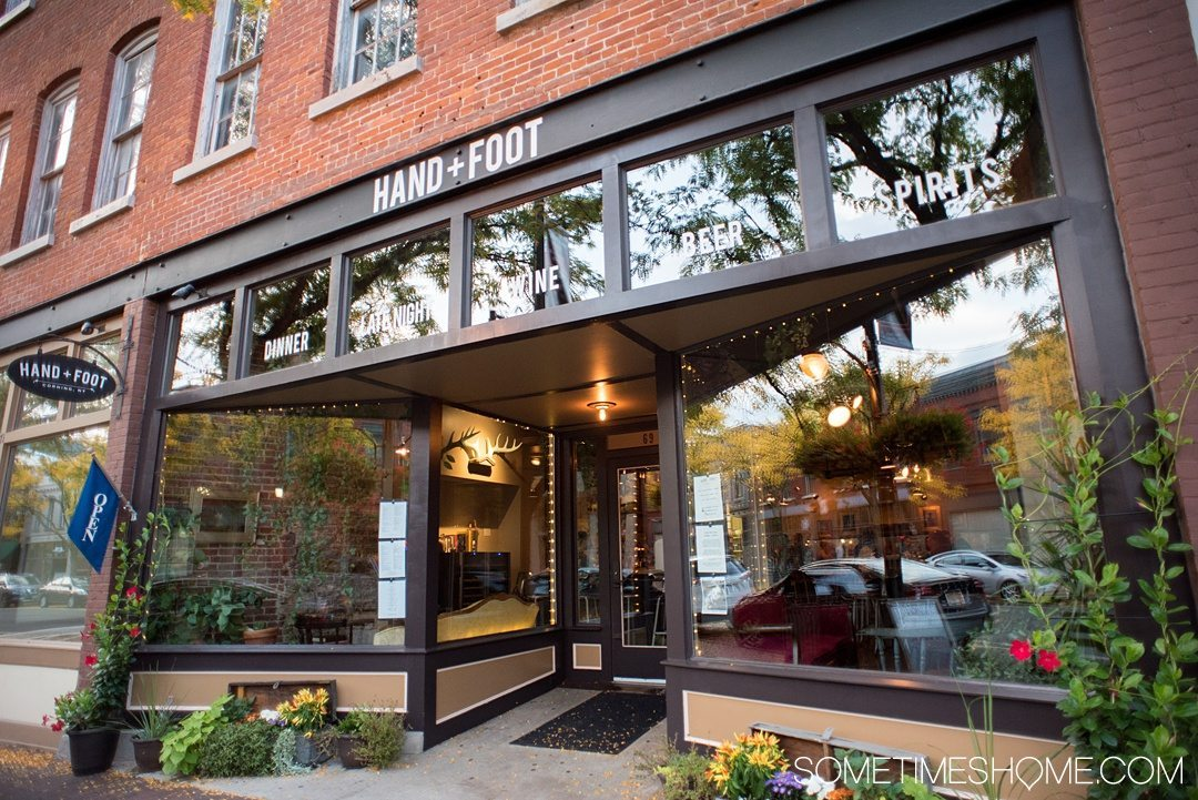 Things to do in Corning NY in the Finger Lakes region on Sometimes Home travel blog. Photo of the outside of Hand and Foot restaurant in their downtown area.