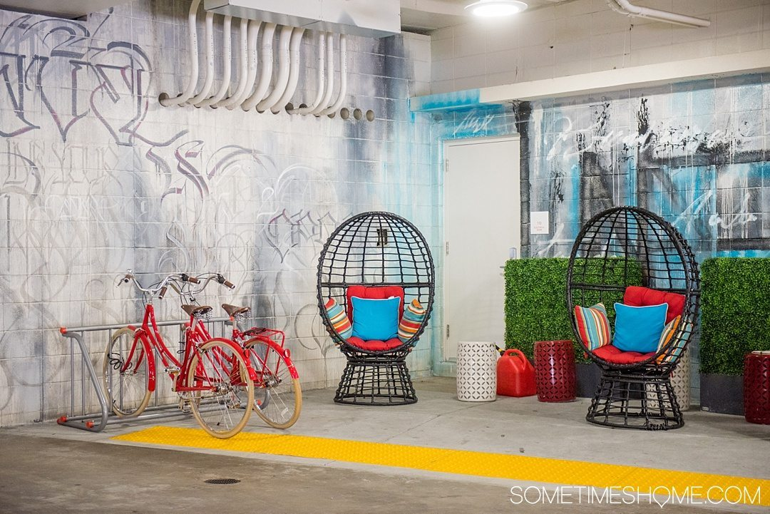 Unscripted Hotel Review Durham in North Carolina. Photos and information on Sometimes Home travel blog. Picture of the interior garage entrance. Bright colors, chairs and graffiti set the stage.