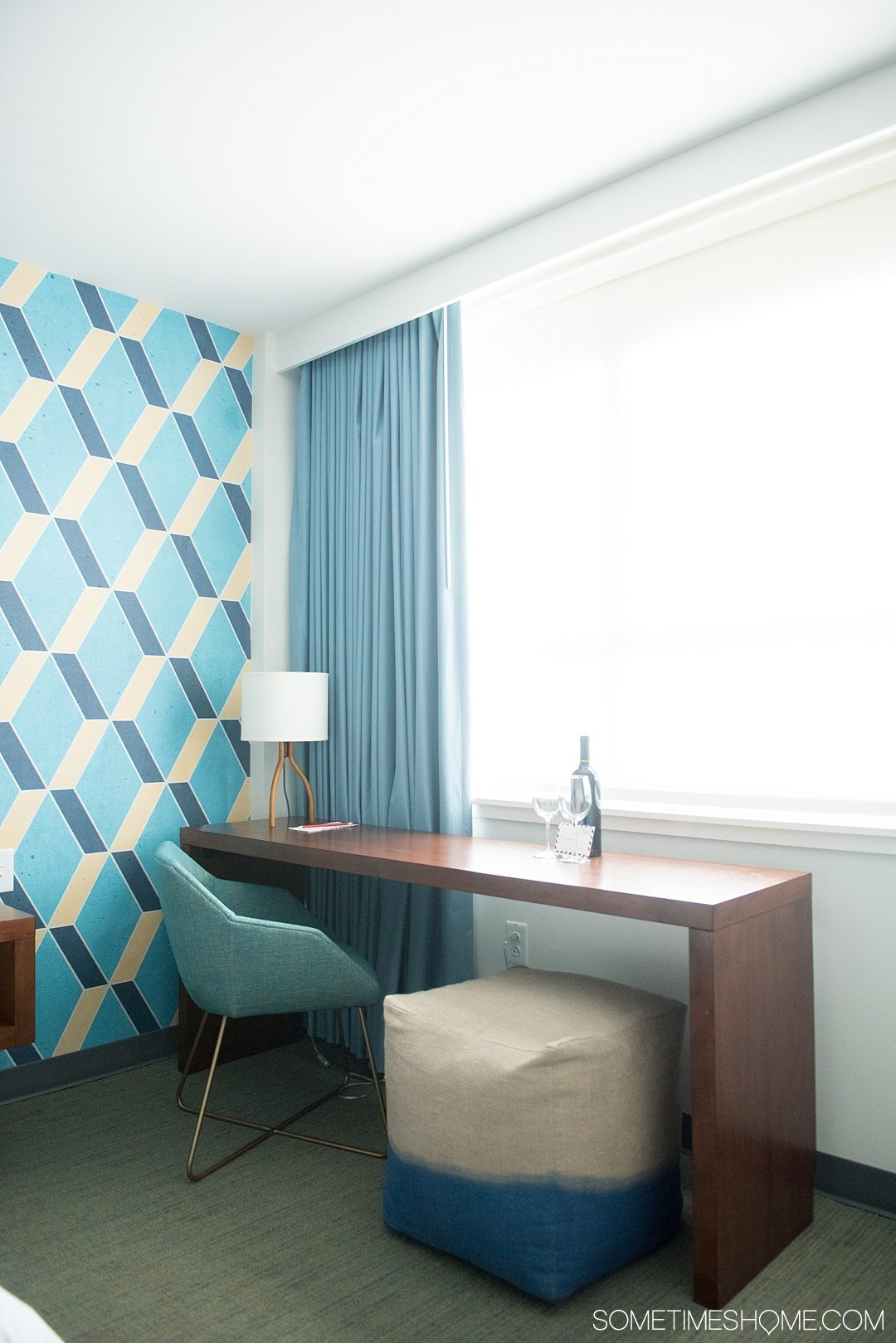 Unscripted Hotel Review Durham in North Carolina. Photos and information on Sometimes Home travel blog. Picture of the hotel room features including a desk area with colorful mid-century modern features and pattern accent wall.