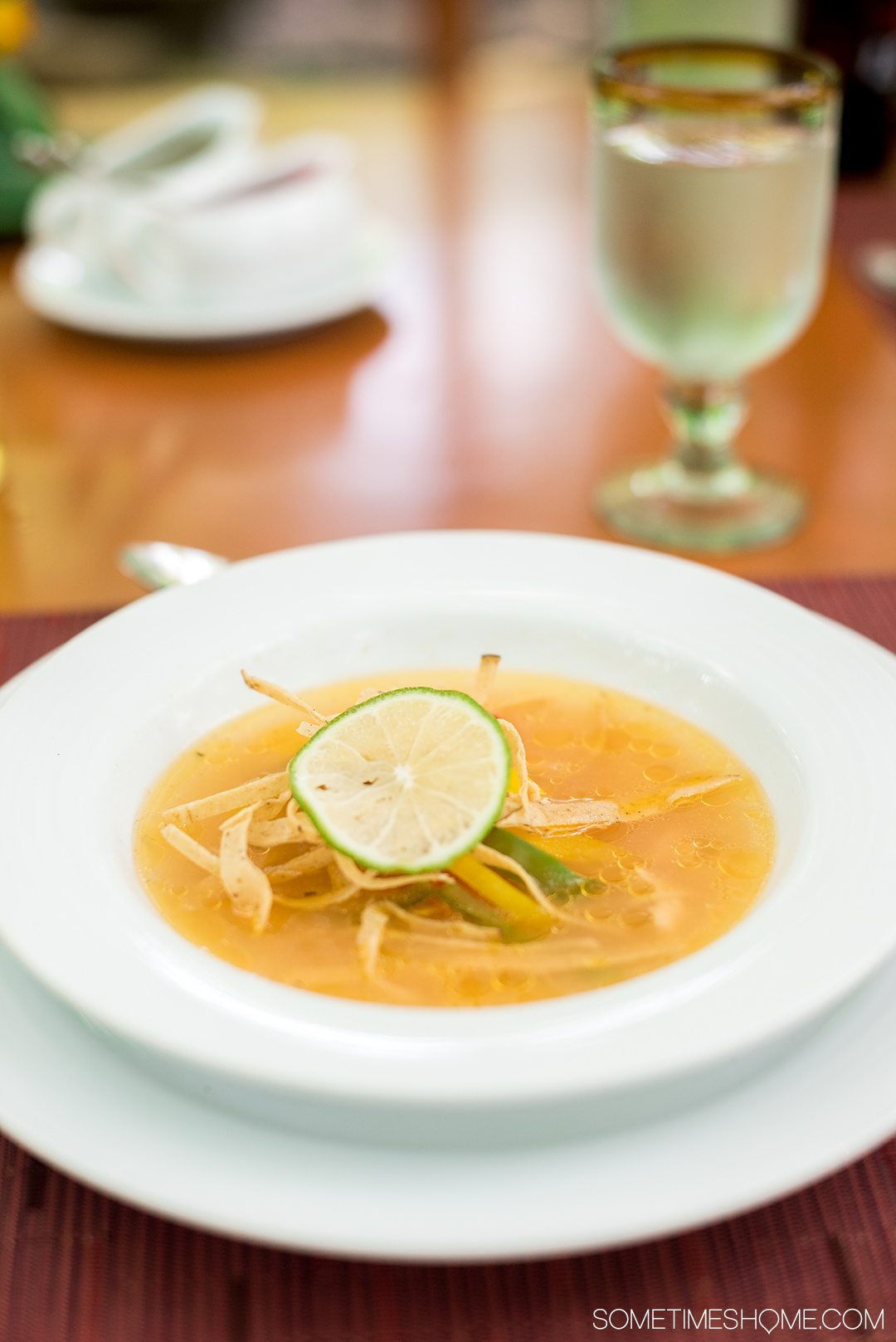 Unique Foods to Try in the Yucatan Peninsula on Sometimes Home travel blog with photos and descriptions of the meals. Picture of Sopa de Lima, a chicken broth based lime soup with red pepper and tortilla strips.