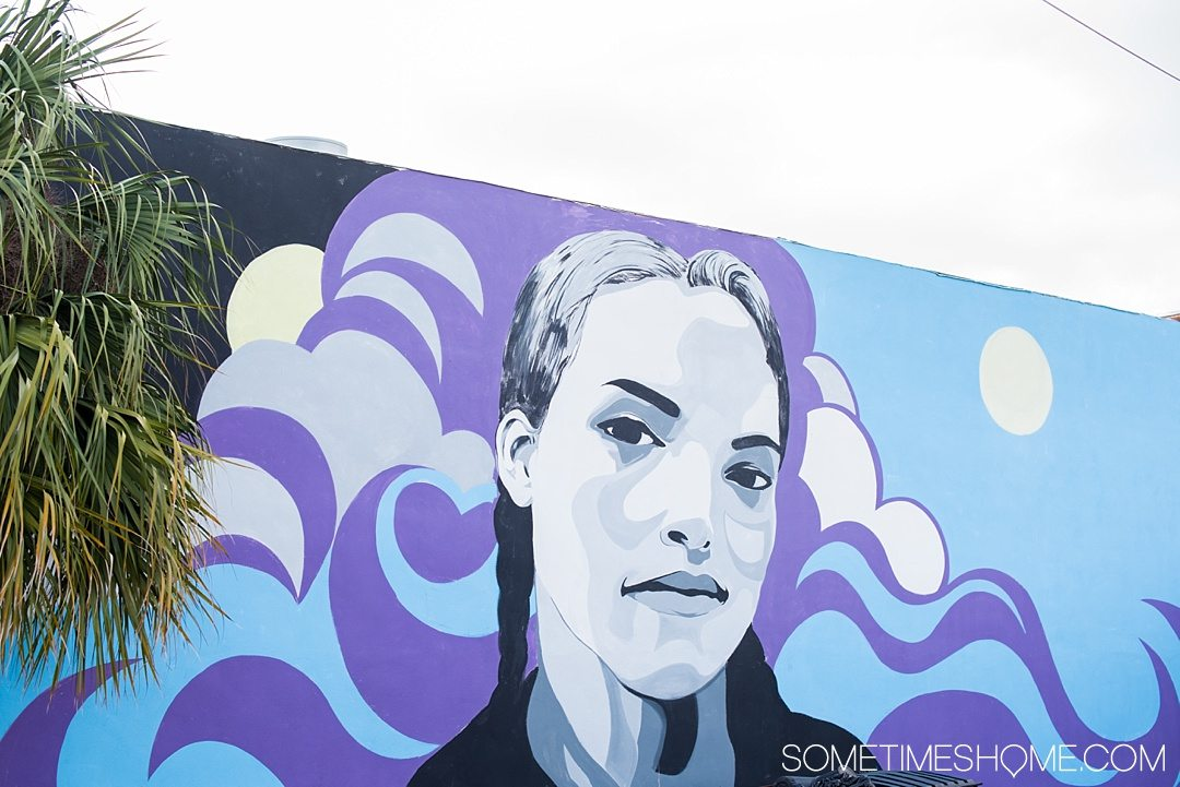 Photography of murals in the city of Tampa Bay, Florida. This is a free activity to partake in and is mostly located in the downtown neighborhood called The Heights. Embark on an adventure to take Instagram worthy pictures as we share where to find the best graffiti art of its kind, including this black and white, purple and blue portrait of a woman. Click through to read which inspired us most and exactly where they're located. #TampaBay #TampaFlorida #StreetArt #Murals #Graffiti