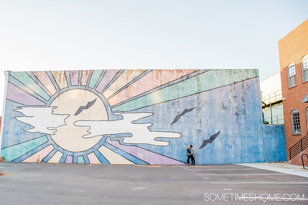 The 12 Best Photography Spots in Durham, North Carolina include art, greenery, a very special part of Duke campus and more. Click through to read the specifics on this downtown colorful, blue sunrise mural on Sometimes Home! #DurhamNC #NorthCarolina #DurhamNorthCarolina #Duke #VisitNC #photographyspots #photography