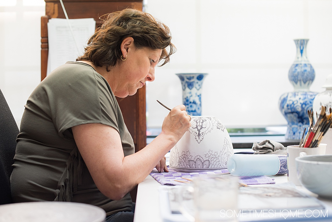 Woman painting Delft Blue pottery at a factory in The Netherlands.