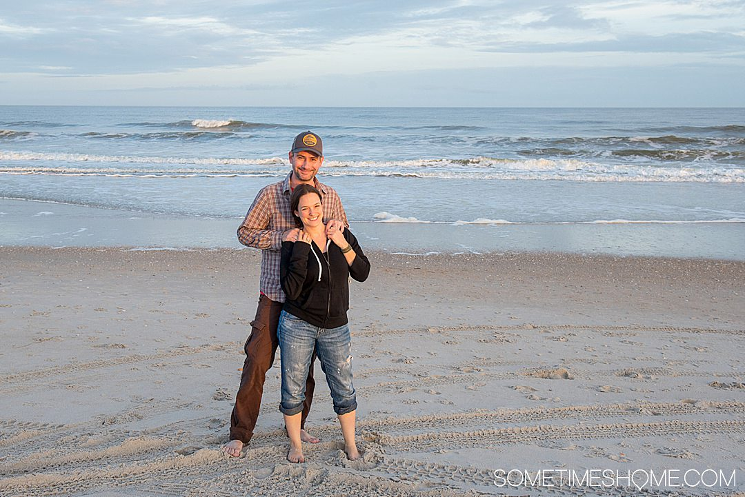A couple on the beach as part of an article for affordable date ideas.
