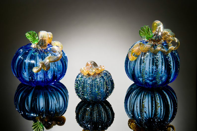 Three glass pumpkins against a black background with lighting.