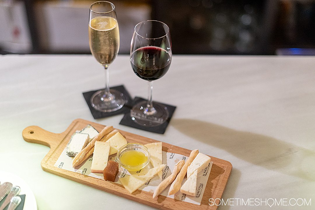 Plate of cheese and two glasses of wine, one white and one red