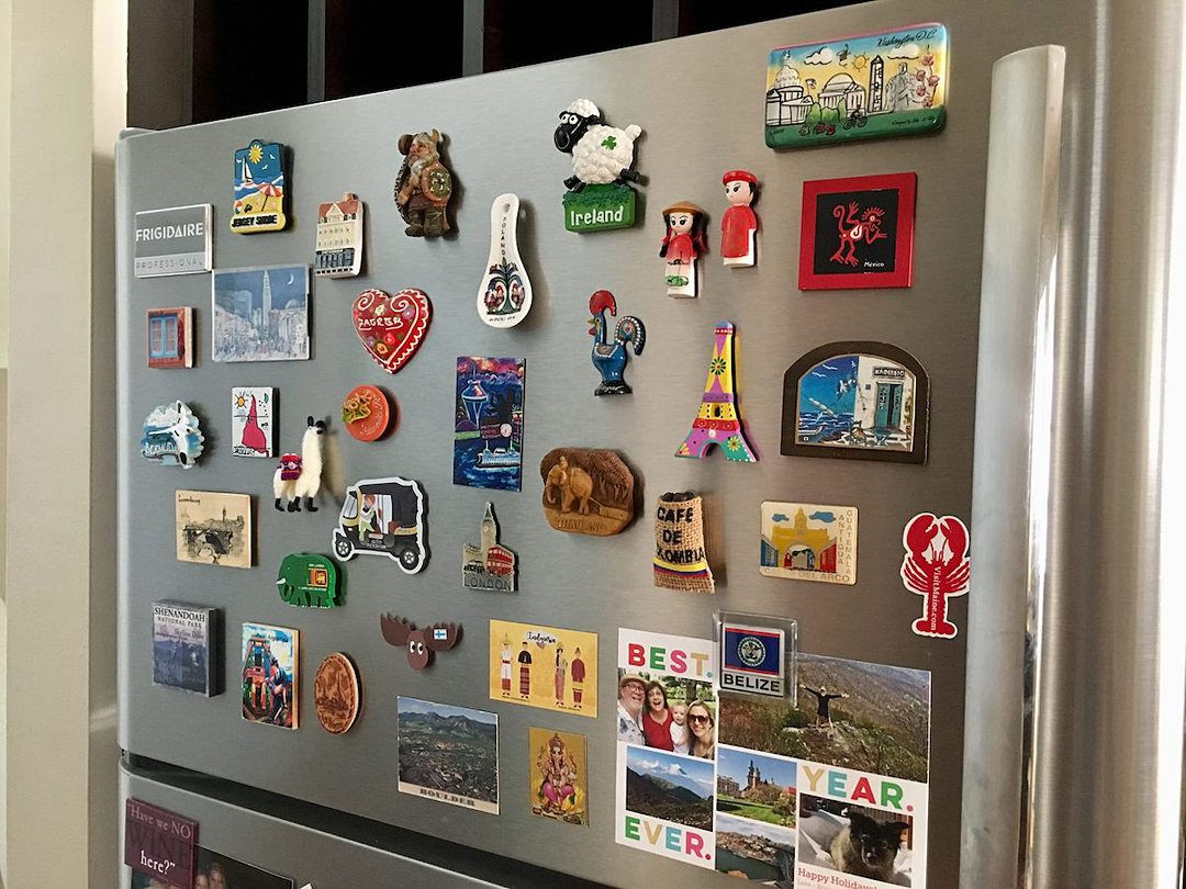 Souvenir magnets from destinations around the world on a refrigerator.