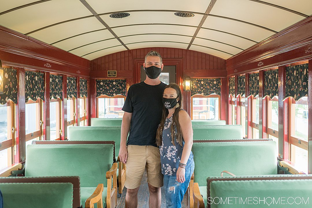 Inside of an old train car and a couple in the middle of the seats