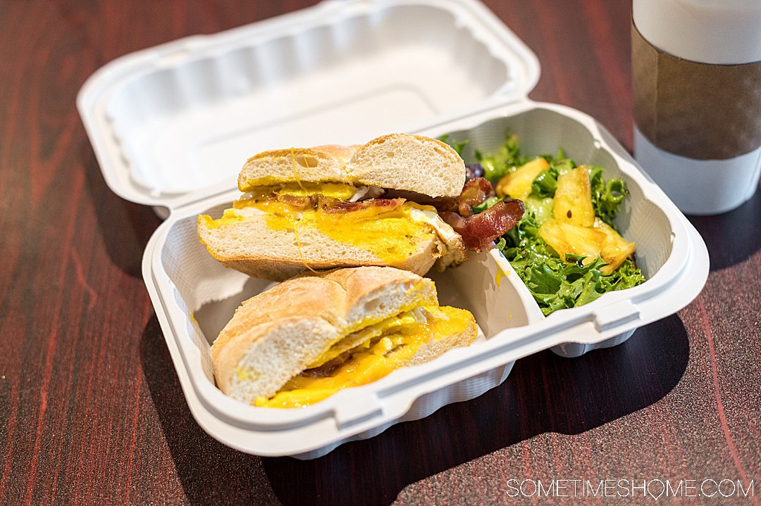 Egg sandwich and side salad topped with pineapple