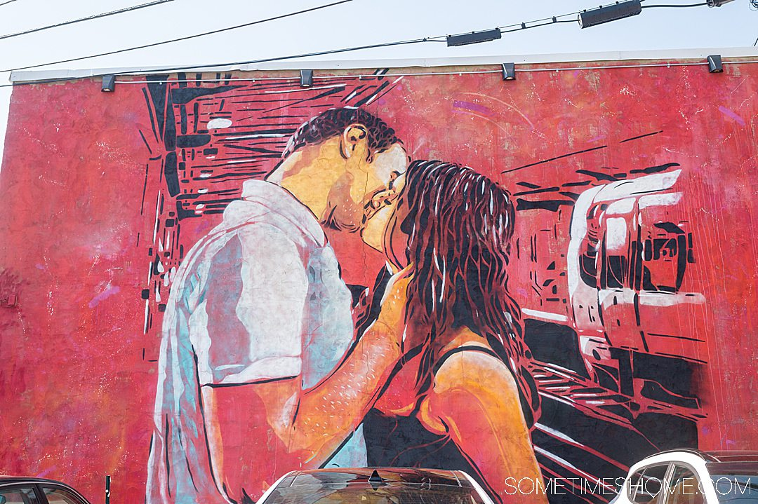 A mural with a red background with a couple kissing