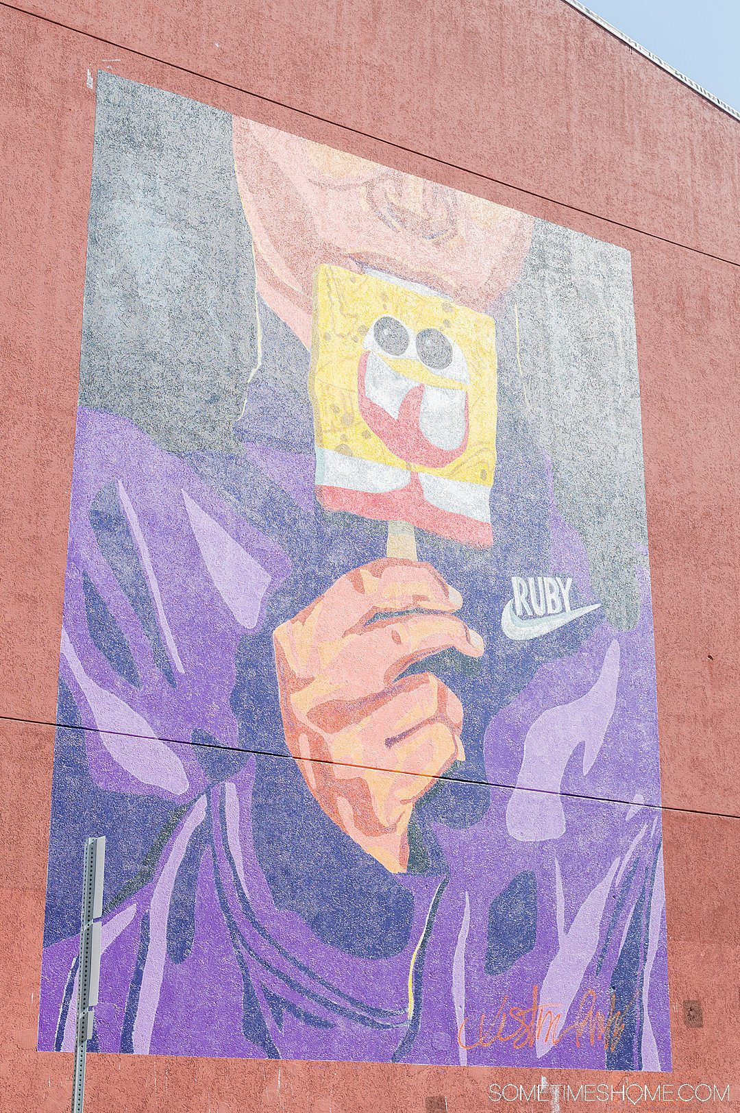 Mural of a person in a purple jacket eating a yellow Sponge Bob pop