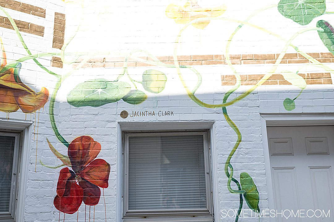 Colorful mural with orange flowers on a white wall