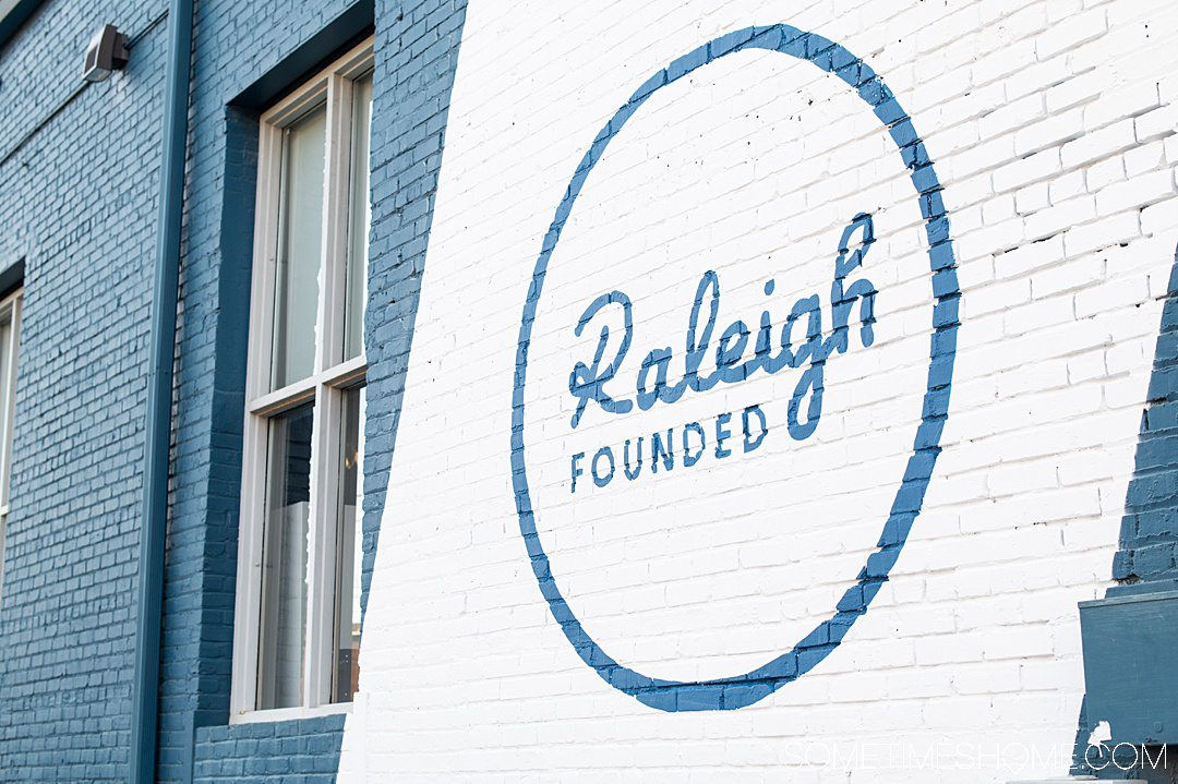 Raleigh founded painted on a wall in blue and white paint.