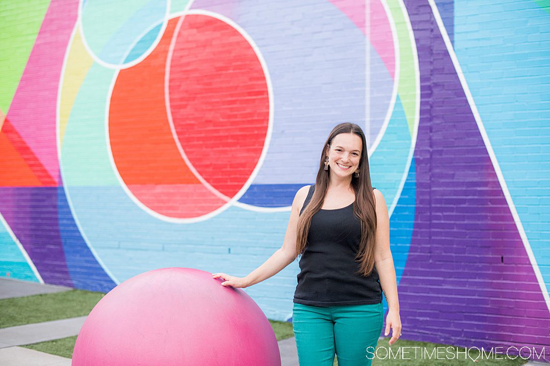 A woman standing in front of a colorful geometric mural in downtown Raleigh with various shapes including circles, triangle, and lines in red, blue, purple, green, yellow and pink