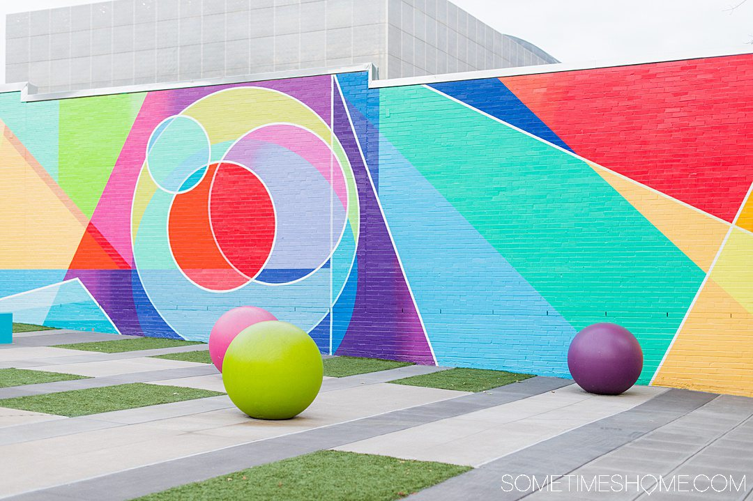 Colorful geometric mural in downtown Raleigh with various shapes including circles, triangle, and lines.