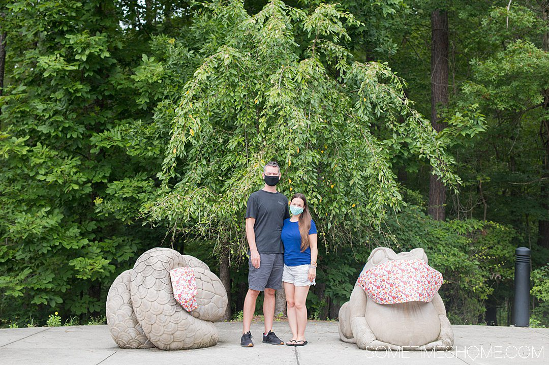 A couple with animal sculptures with masks on in Chapel Hill.