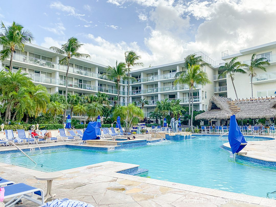 A view of the blue pool and palm trees in the distance at the Marriott Key Largo with blue skies and white clouds.