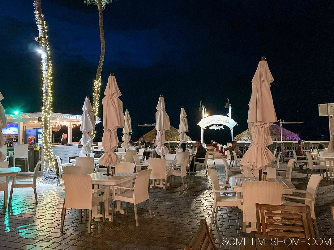 Dark sky and collapsed oversized patio umbrellas with table and chairs at an outdoor restaurant.