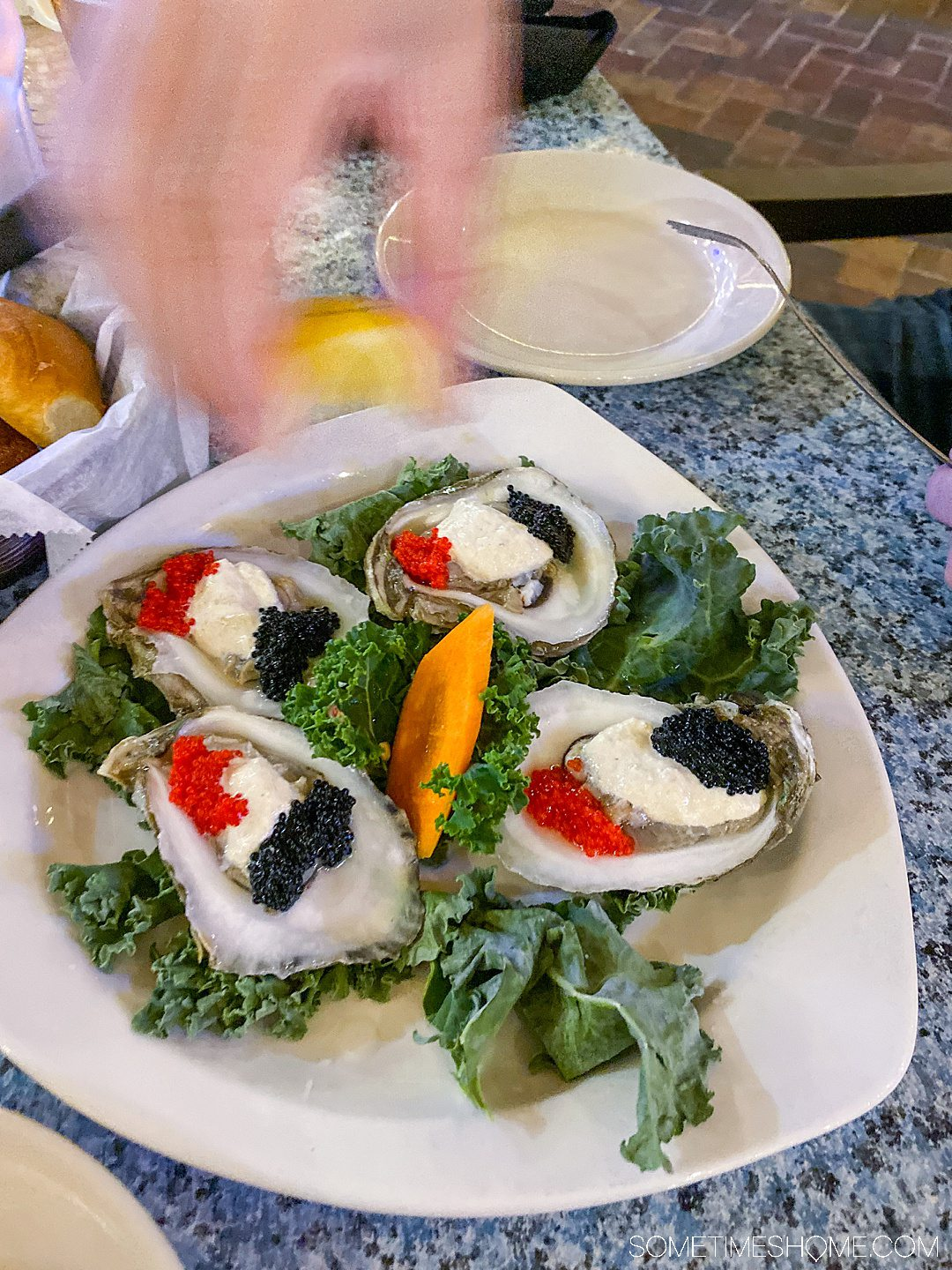 A place of four oysters and a hand in motion squeezing a lemon above the plate.