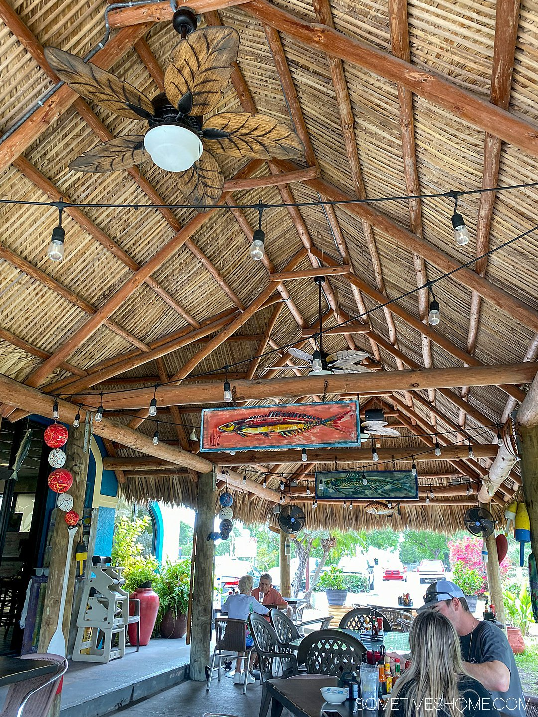 A roof above diners at a restaurant in Key Largo, FL and two fish paintings in the rafters.