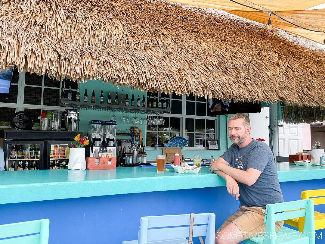 A man at a blue and turquoise painted bar in Florida.