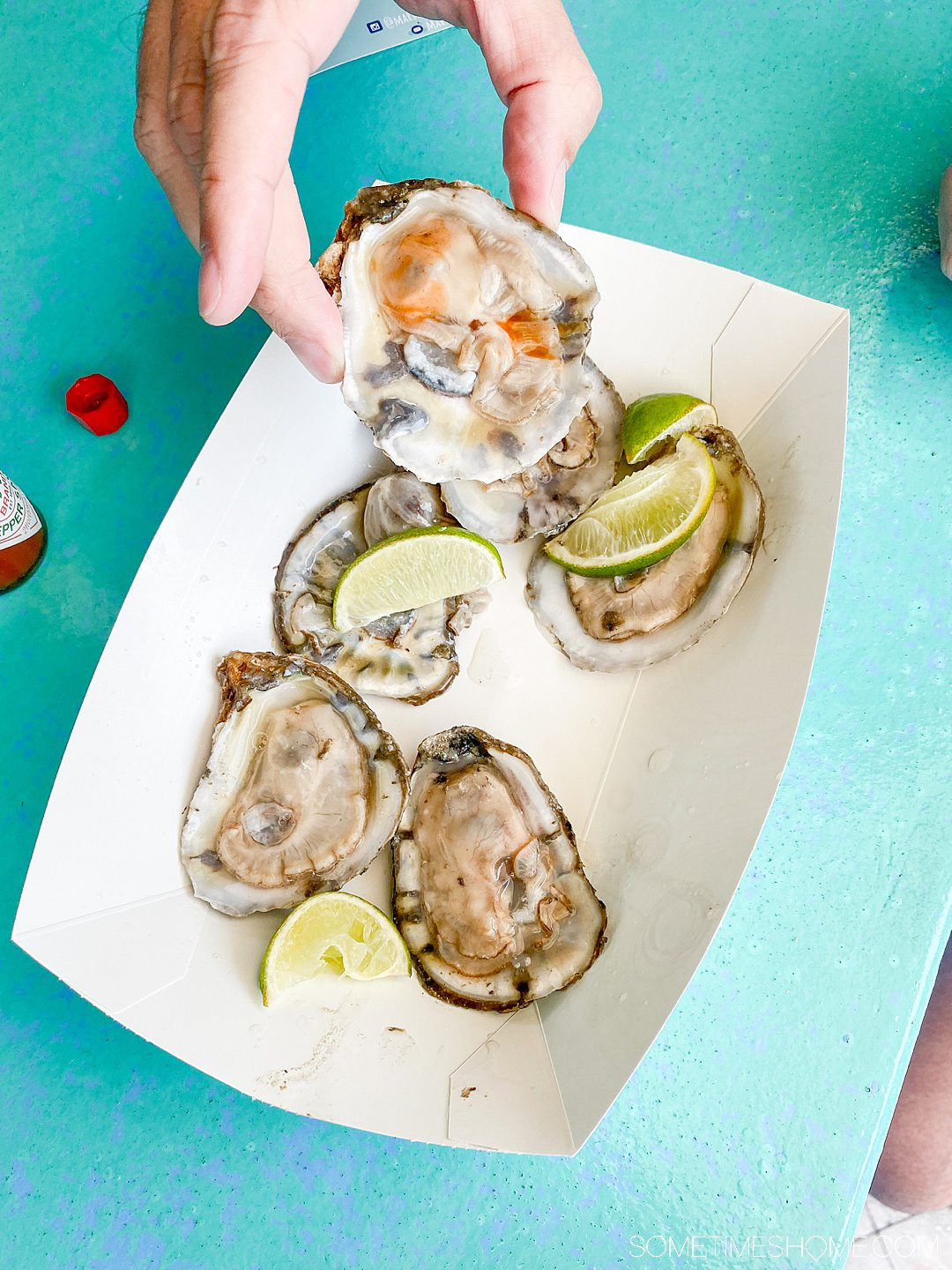 6 oysters with a paper tray, and a man holding one of them.