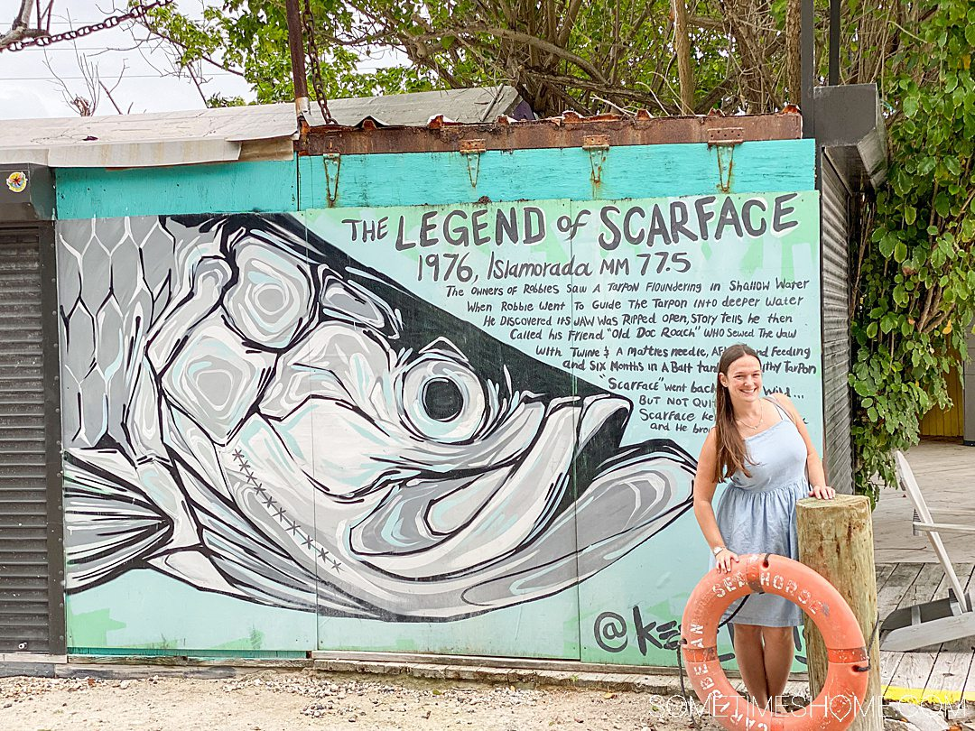 A woman posting by a life saver tube on land, with a painting of a fish behind her.
