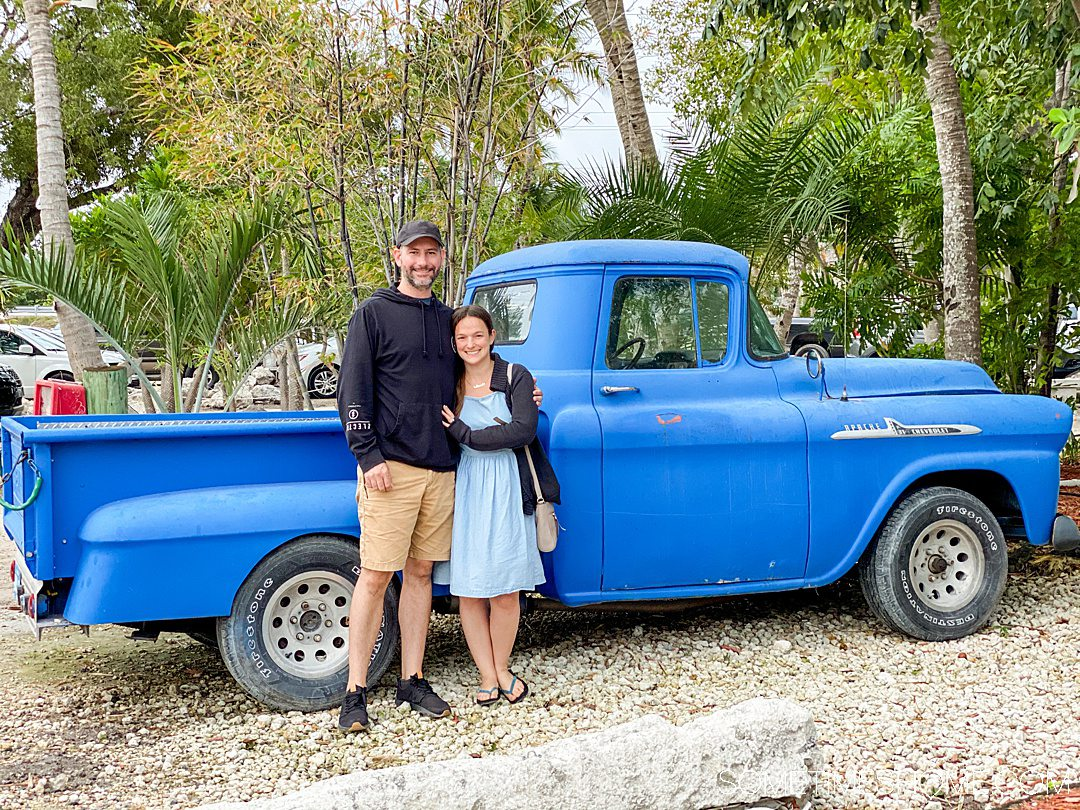 A man and a woman in front of a bright blue pick up truck with greenery behind it.