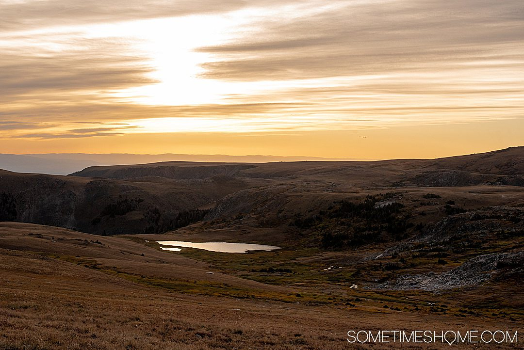 Sunset reflecting on a lake in the distance of Beartooth Highway in Montana, with silhouetted dark mountains.